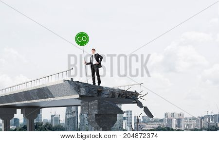 Confident businessman in suit holding green go sign while standing on broken bridge with cityscape on background. 3D rendering.