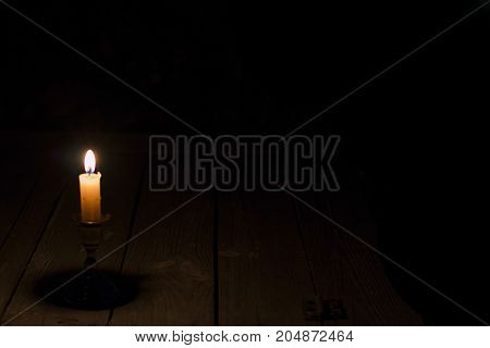 Burning candle on wooden table in darkness. Halloween background.