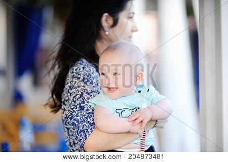 Young mother holding her smiling baby boy. Parenthood concept. Mommy and son