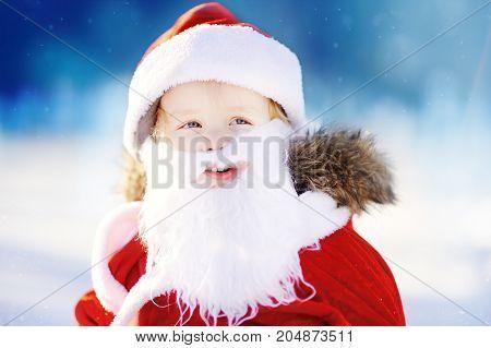 Funny Little Boy Wearing Santa Claus Costume In Winter Snowy Park