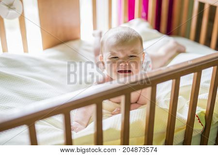A Close-up portrait of a crying cute baby in the crib at home
