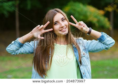 Portrait of a girl on a dark background, the girl shows two fingers at the face