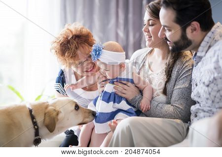 A Close up portrait of three generations of women being close, grandmother, mother and baby daughter at home
