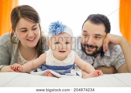 A Happy family, mother, father and baby on the white bed