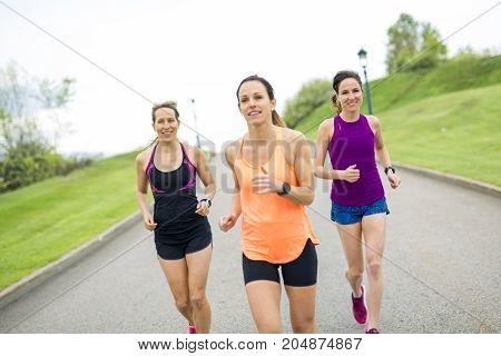 Three nice relaxed runners on a paved jogging daylight