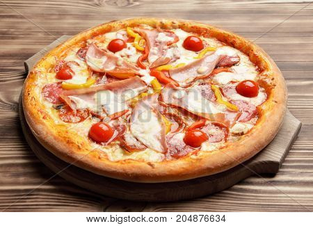 Hot big whole tasty pizza with melting cheese bacon tomatoes ham paprika on a rustic wooden table
