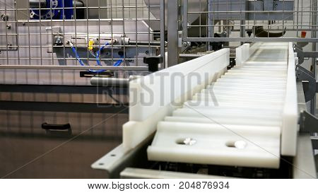 Food factory automated robotic machine. Conveyor product line for cooking and packing rations and food packs. Robotics and automatic lines used instead of human labor on factories and plants.
