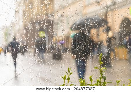Abstract blurred silhouette of men under umbrella, back tu us. city street seen through raindrops on window glass, blurred motion background. Concept of seasons, weather, modern women in city