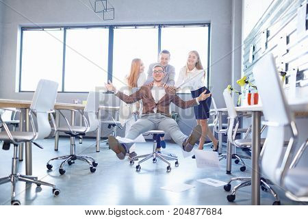 Excited businessman throwing away papers with his colleagues on a blurred office background. Happy young managers having fun.