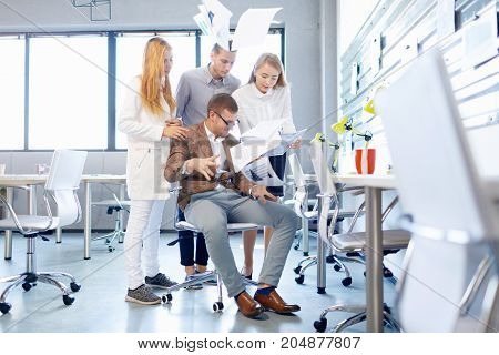 Young, irresponsible business staff members messing with papers on the blurred office background. Modern paperwork concept.
