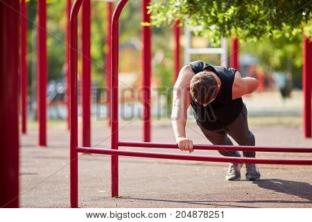 Brunette male working out on horizontal bars in a park on a blurred background. Street sports equipment. Copy space.