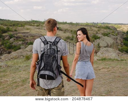 Attractive, stunning girlfriend with long hair and a modern, casual boyfriend walking and flirting on a blurred natural background. A couple of young hikers near hills. Relationship and love concept.