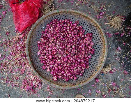 Close up of a red onions insid eof a wooden tray in a street market in Hue, Vietnam.