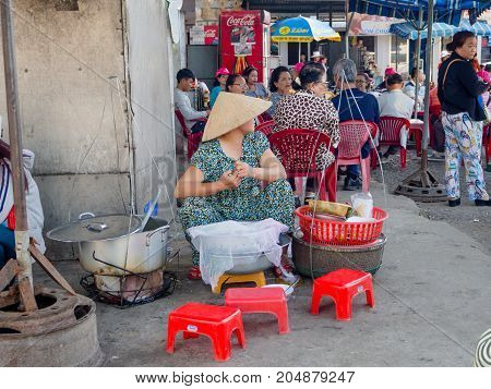 Hue, Vietnam - September 13 2017: Unidentified woman in the streets selling food, located in Hue in Vietnam.