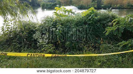 yellow caution tape with lake and fountain and trees
