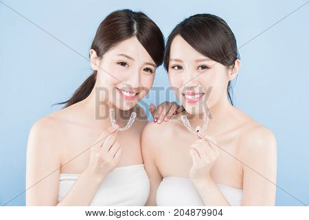 two beauty woman take invisible braces on the blue background