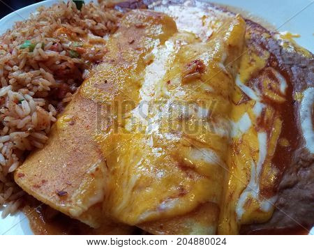 enchiladas with rice and beans and cheese on a plate