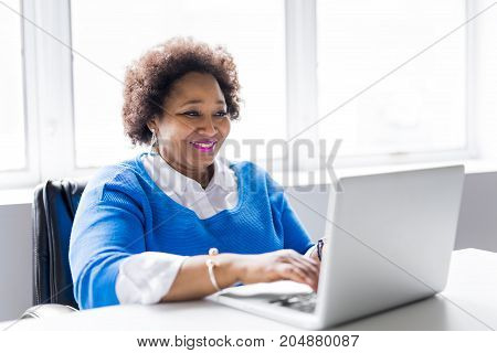 A Portrait of cheerful business African-American working on laptop