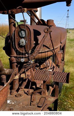 The electric box, gear shift lever, engine mounting,  and foot brake pedals  of an old rusty tractor