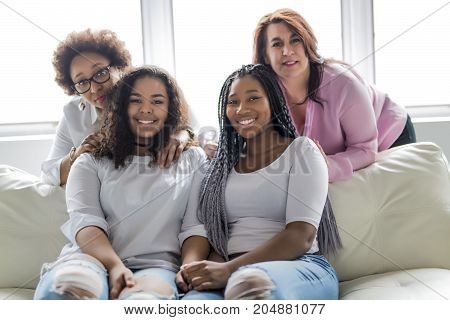 Two family Friends Sitting On Sofa Together having fun