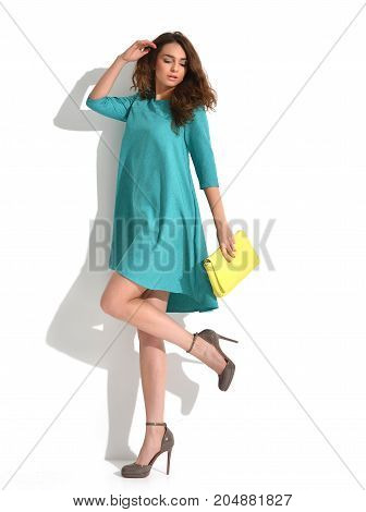 Beautiful woman walking running in light blue fashion body dress cloth with yellow  hand bag clutch on a white background