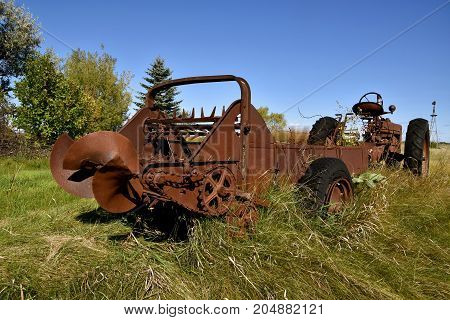 An old rusty manure spreader and tractor are forgotten in the long grass