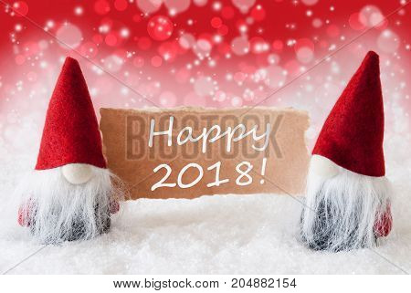 Christmas Greeting Card With Two Red Gnomes. Sparkling Bokeh And Christmassy Background With Snow. English Text Happy 2018
