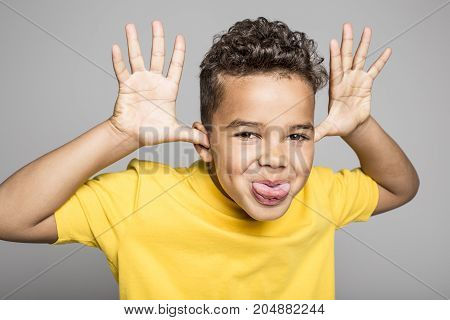 An Adorable african boy on studio gray background