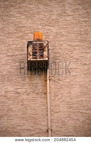 An old battered and rusty speaker of a warning light on a house wall.