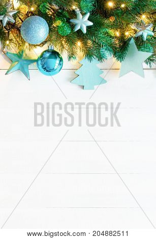 White Wooden Background With Copy Space. Vertical Christmas Banner With Turquoise Christmas Decoration Like Balls, Tree And Star. Fir Branches With Fairy Lights And Bokeh.