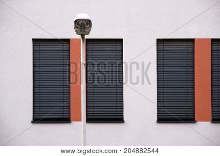 The modern facade of a modern residential building with windows with metal blinds and street lighting.