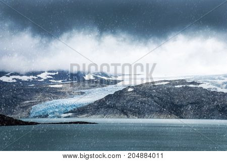 Glacier In Norway With Ice And Snow. Mountain With Lake And Clouds And Snowflakes
