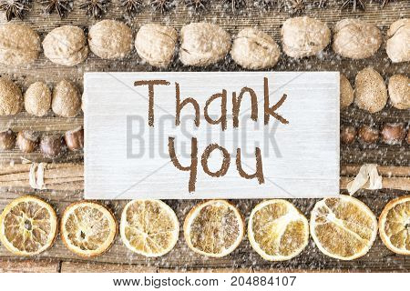 Sign With English Text Thank You. Christmas Food Flat Lay With Walnut, Hazelnut, Cinnamon Sticks And Orange Peel. Brown Wooden Background With Snowflakes
