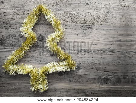 Golden Tinsel Christmas Tree On Gray Wooden Background. Copy Space For Advertisement.