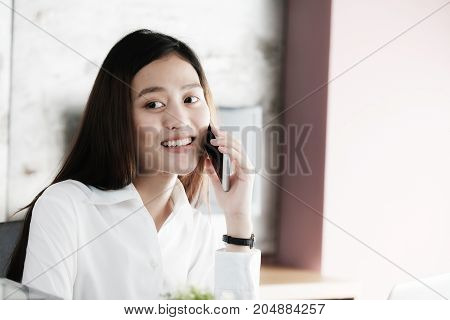 Young businesswoman talking smart phone at office background business communication concept