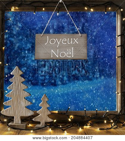 Sign With French Text Joyeux Noel Means Merry Christmas. Window Frame With Winter Landscape With Snow. View To Snowy Trees Outside With Snowflakes. Christmas Tree And Fairy Lights.