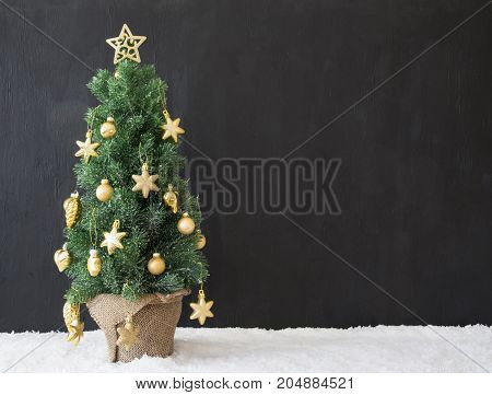 Copy Space For Advertisement. Golden Decorated Christmas Tree With Black Concrete Or Cement Background. Modern Urban Style With Snow