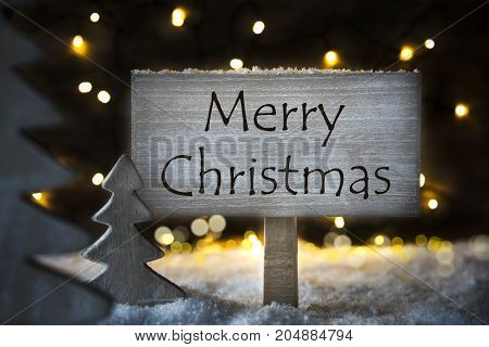 Sign With English Text Merry Christmas. White Christmas Tree With Snow And Magic Glowing Lights In Backround. Card For Seasons Greetings.