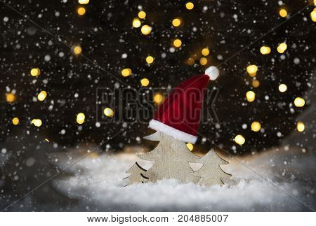 Wooden Christmas Tree With Santa Hat On White Snow. Glowing Lights In Background With Snoflakes.