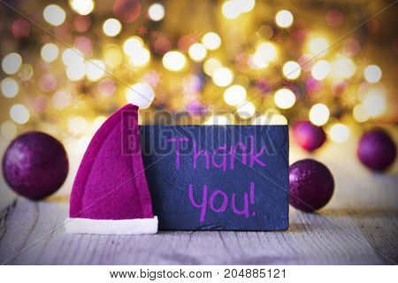Plate With English Text Thank You. Purple Christmas Ball Ornaments And Santa Claus Hat. Wooden Background With Lights