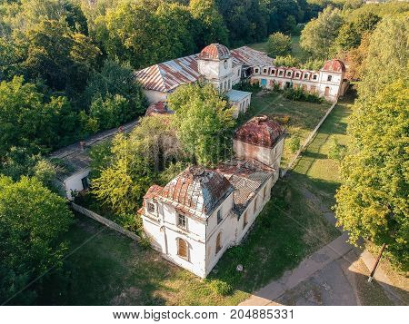 Aerial view on ruins of abandoned mansion in summer sunset lights.