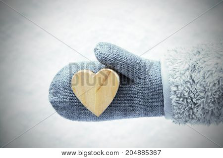 Wool Glove With A Wooden Heart. White Snow In Background.