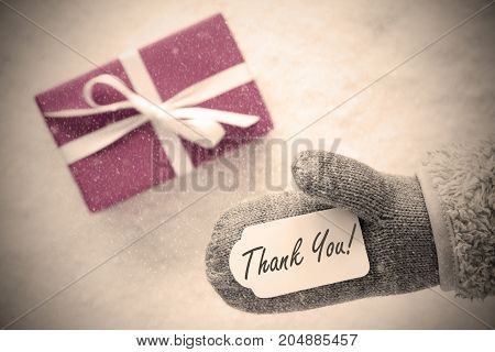 Glove With Label With English Text Thank You. Pink Or Rose Gift Or Present On Snow In Background. Seasonal Greeting Card With Snowflakes And Instagram Filter