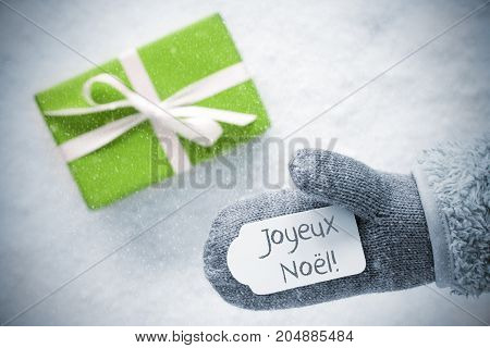 Glove With Label With French Text Joyeux Noel Means Merry Christmas. Light Green Gift Or Present On Snow In Background. Seasonal Greeting Card With Snowflakes.