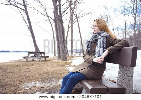 A Young lonely woman on bench in park