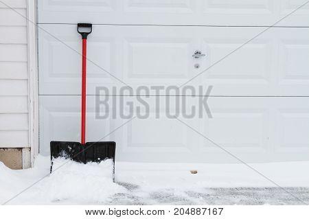 a snow shovel leaning on garage door.