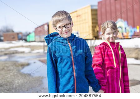 two child brother sister close to a train