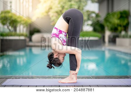 Beautiful young Asian woman doing yoga exercise with uttanasana posing near swimming pool. Healthy lifestyle and good wellness concepts