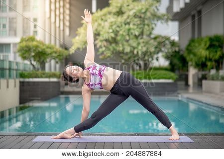Beautiful young Asian woman doing yoga exercise with Trikonasana posing (extended triangle pose) near swimming pool. Healthy lifestyle and good wellness concepts