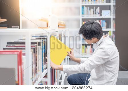 Young Asian man university student choosing book in library education research and self learning in university life concepts